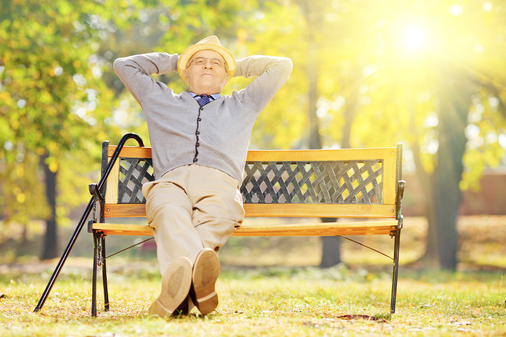 Older man sitting on a bench while basking in the sun